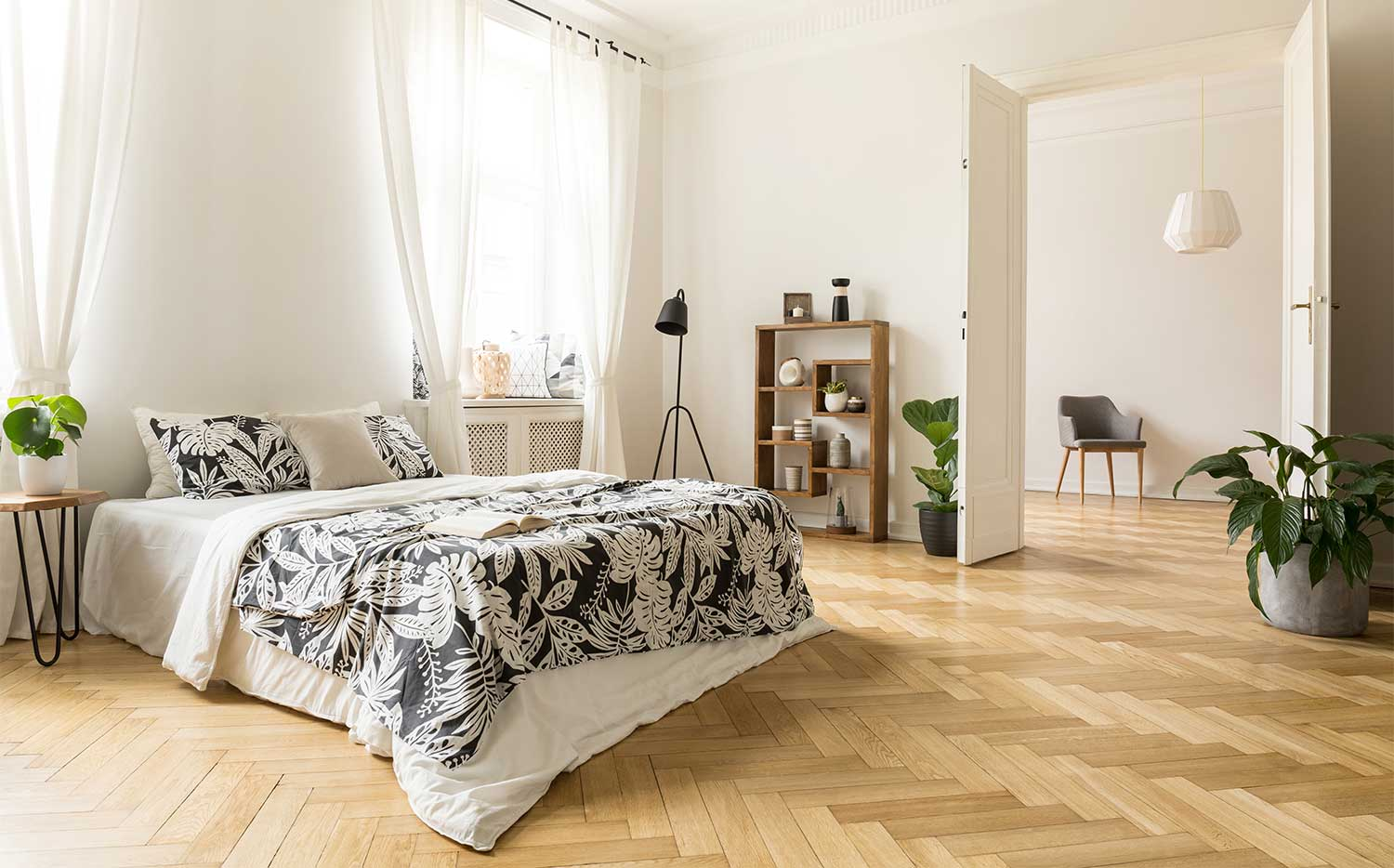 Herringbone engineered hardwood flooring in a modern bedroom.
