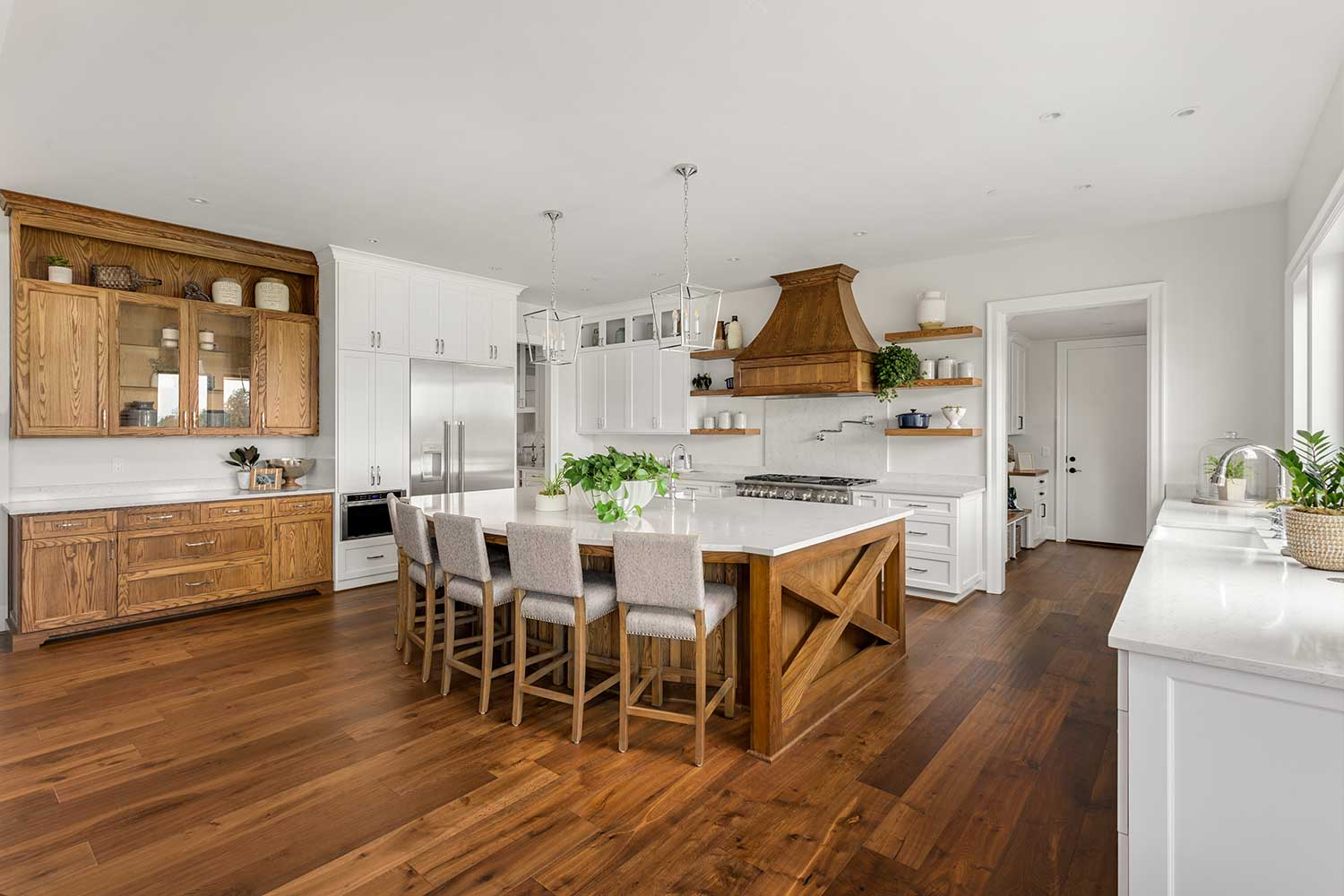 A kitchen with brown engineered hardwood flooring and white cabinets.
