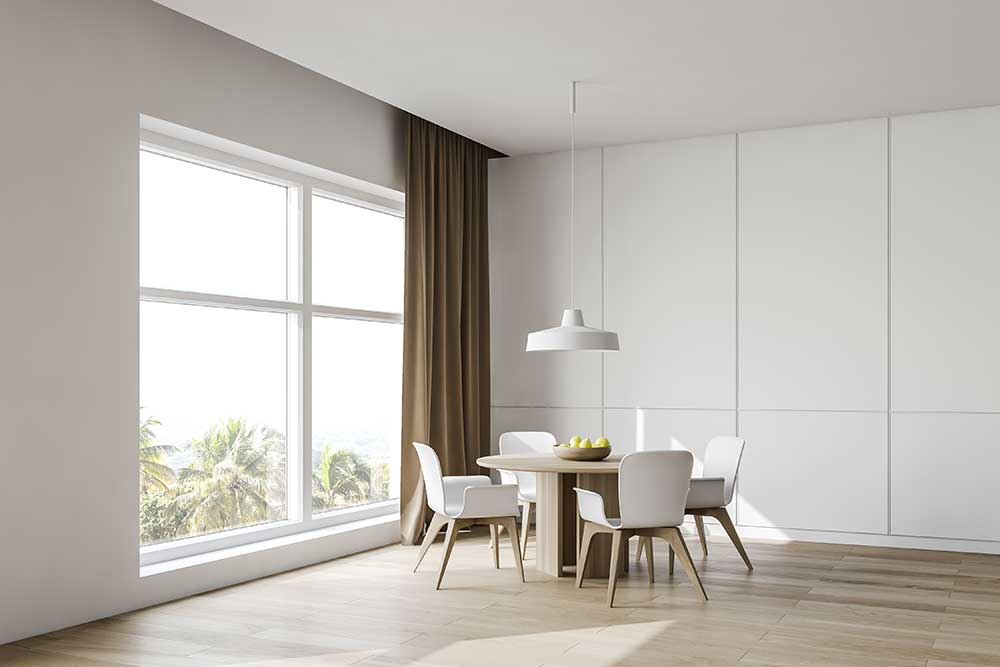 Modern dining room with a light laminate floor and a huge window.