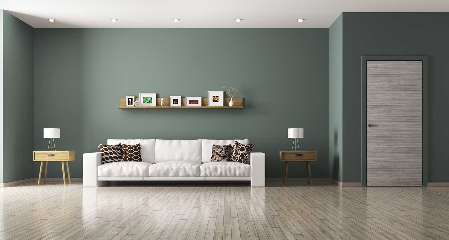 Light-colored laminate flooring in a living room with green walls and a white sofa.