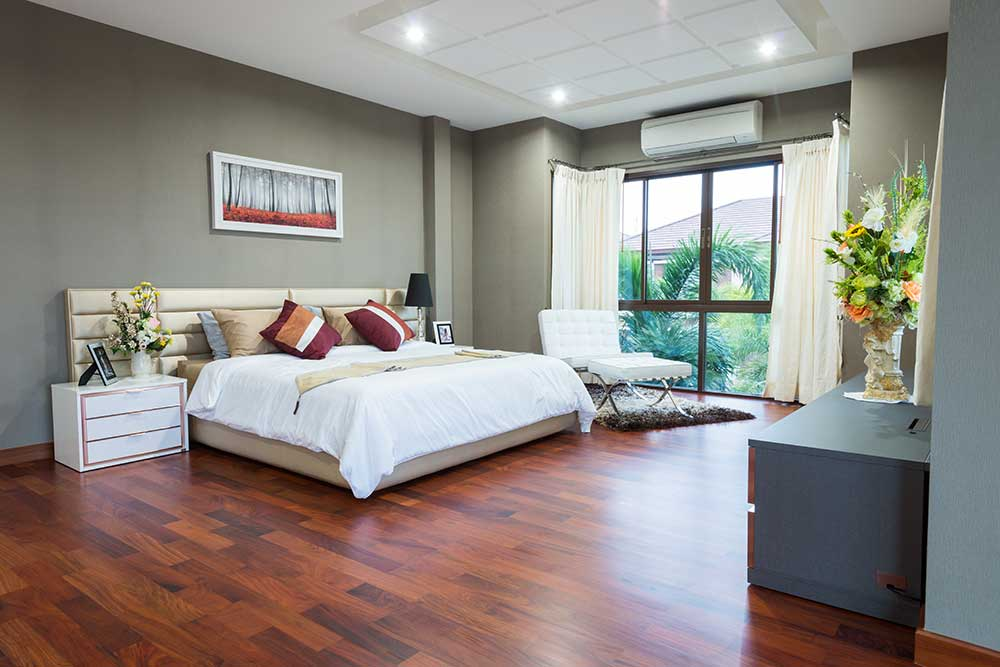 Cherry-colored solid hardwood flooring installed in a bedroom.