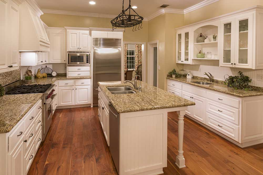 Classic kitchen with solid hardwood flooring and white cabinets.