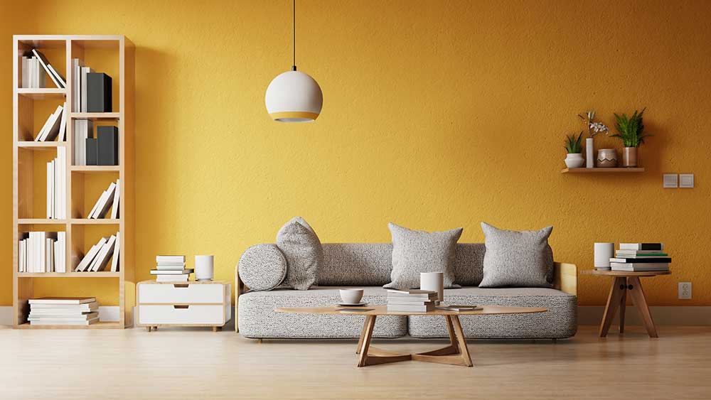 Modern living room flooring with a yellow wall and gray couch.